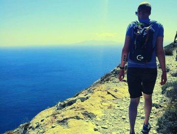 Man met een Direct Result rugzak op stap naast de zee op een rots